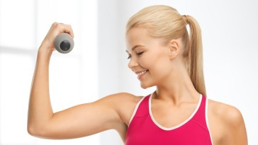 fitness and home concept - young sporty woman with light dumbbell