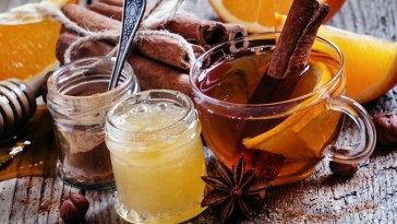 Winter tea with orange, honey and cinnamon in a glass cup on the